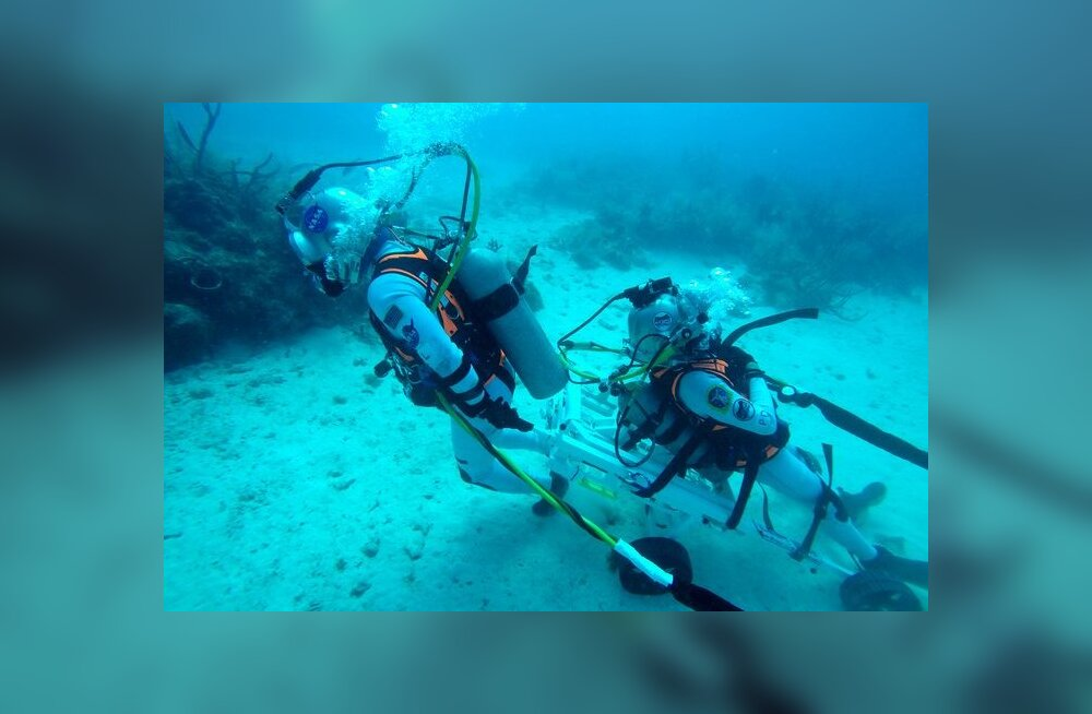 NASA astronaut Kjell Lindgren tirib ESA astronauti Pedro Duqued, kes lebab päästeseadmel, 20 m sügavusel mere põhjas. Merepõhi meenutab suurepäraselt Kuu pinnast, samuti on võimalik simuleerida vee all erineva tasemega raskusjõudu.