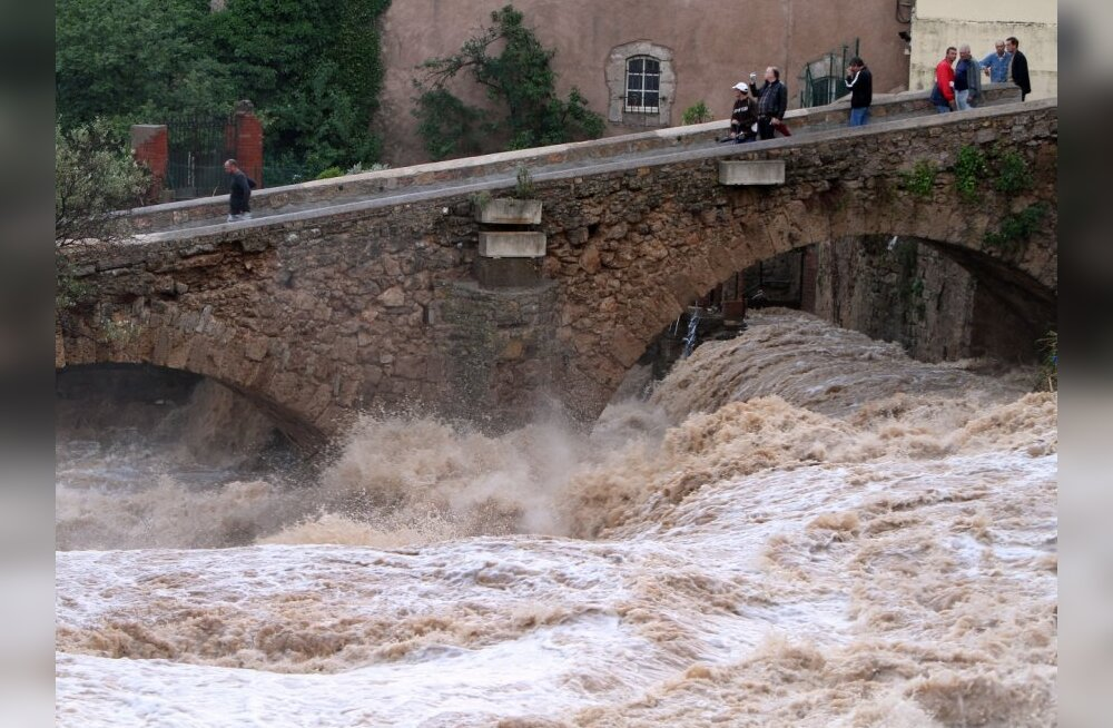People look at La Nartuby river at a bridge crossing after heavy flooding in Trans en Provence, south eastern France, June 16, 2010 the morning after rising water from unusually heavy rains that hit the region caused a river to overflow. At least nine peo
