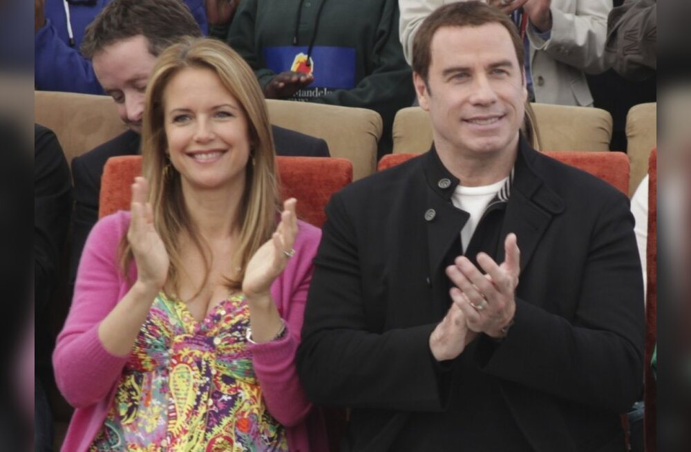 John Travolta and his wife Kelly Preston, left, during a visit to the  Nelson Mandela Children's Fund headquarters in Johannesburg, Saturday, June 12, 2010. Travolta is in the country for five days a s an official goodwill ambassador for the Australian so