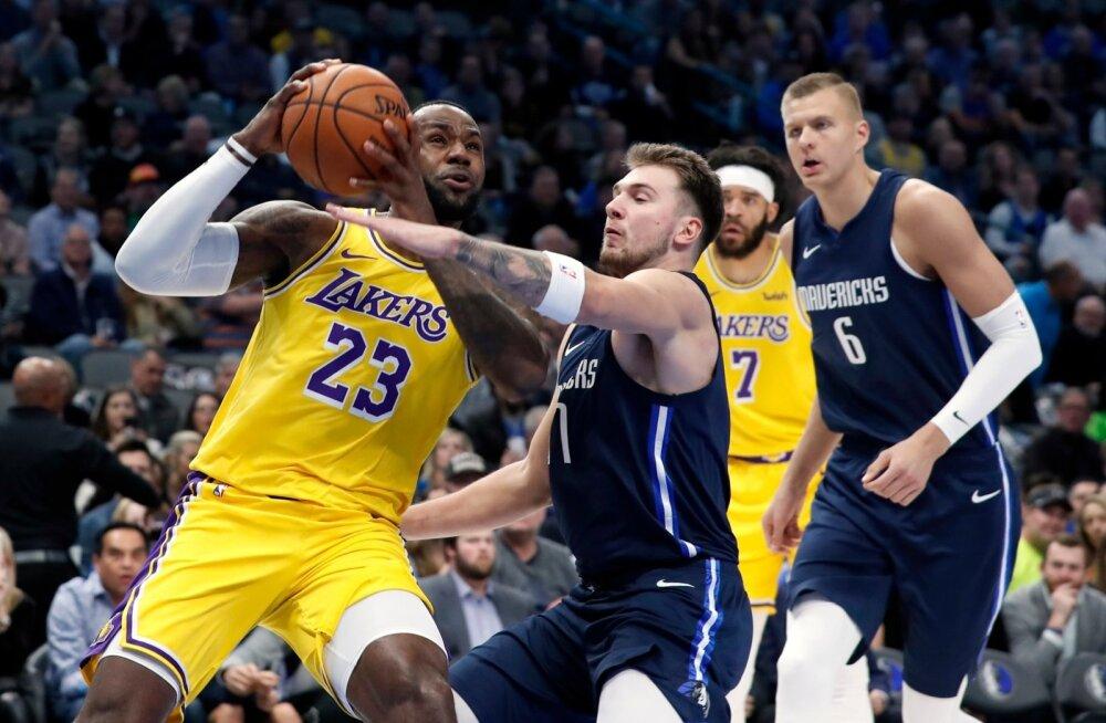 Luka Doncic proovib takistada LeBron Jamesi. Olukorda jälgib eemalt Kristaps Porzingis.