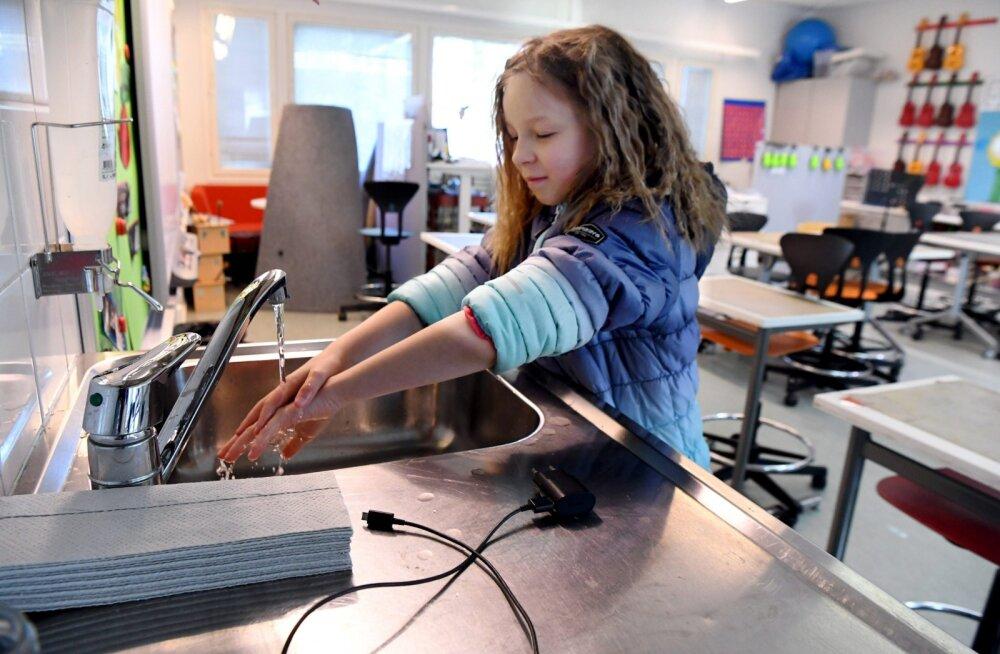 Soomes algab uus kooliaasta: Helsingi Kalasatama koolis õpib osa õpilasi võimlas, täiskasvanud hoiavad üksteisest eemale