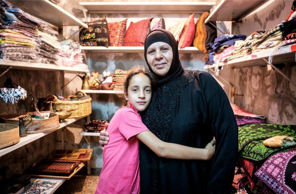 Leila Awawdeh lapselapsega oma poe uksel. Awawdeh ei julge Hebronist lahkuda, sest tagasi tulles ei pruugi ta enam oma majja pääseda.