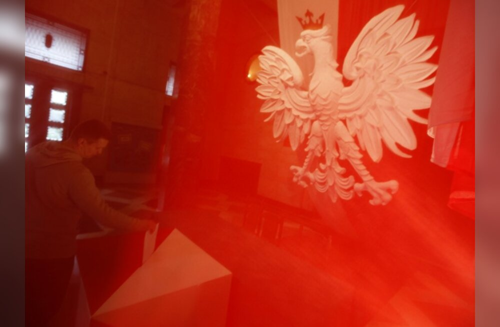 A man is seen through a Polish national flag as he casts his vote at a polling station in Warsaw during presidential elections June 20, 2010. Poles began voting for a new president on Sunday in an election that will help shape the pace of economic reforms