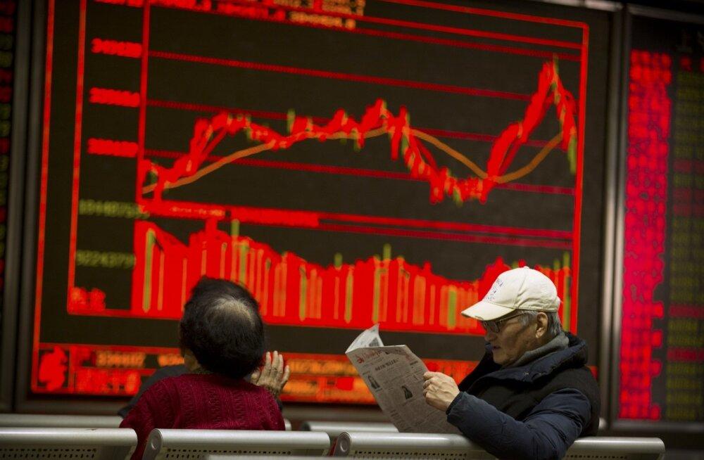 Hiina investor Pekingi maaklerfirma ekraani ees ajalehte lugemas.