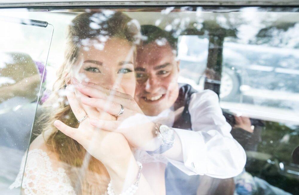 Luisa ja Taavi Rõivas näitavad pulmaautos olles esimest korda oma sõrmuseid.