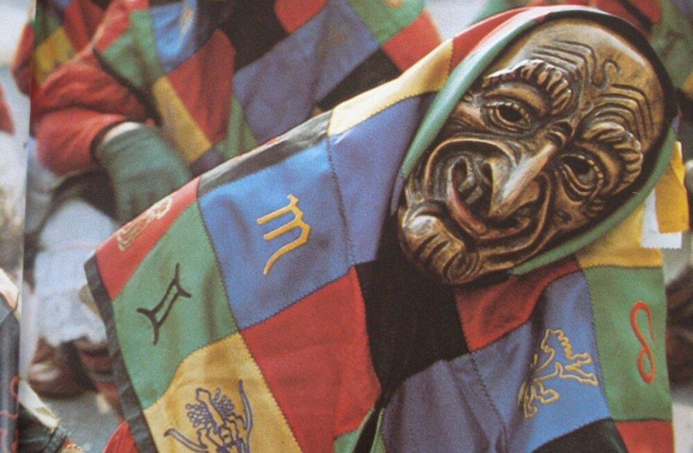 Traditsiooniline värvilistest lapikestest rõivaese, mille juurde käib ühest puutükist voolitud mask.