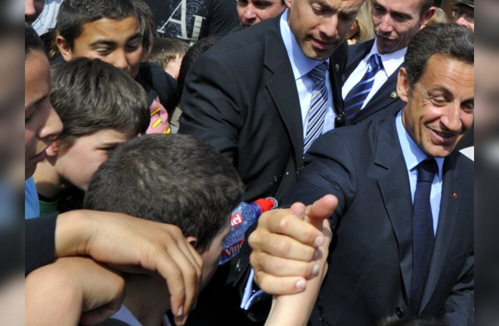 A bottle of water (C) is seen as it drops near France's President Nicolas Sarkozy who shakes hands with pupils as he arrives at the Charles Fauqueux college in Beauvais, May 25, 2010.   REUTERS/Philippe Wojazer  (REUTERS - Tags: POLITICS EDUCATION)