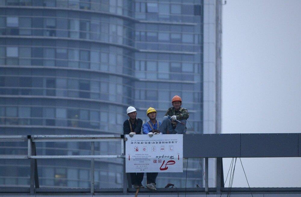 Ehitustöölised Shanghai hoone katusel.