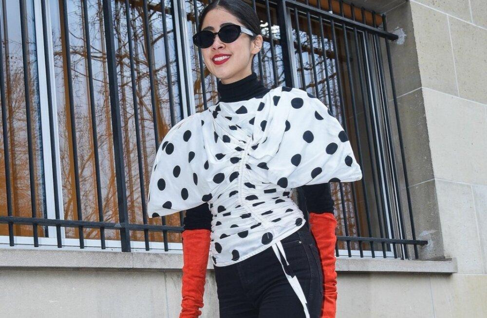 Sotsiaalmeedia spetsialist ja moemaailma mõjutaja Denni Elias ühendab puhvkäistega ja kroogetega pluusi lihtsate mustade teksadega. Erkpunased kindad teevad komplekti šikiks ja päikeseprillid annavad glamuuri.