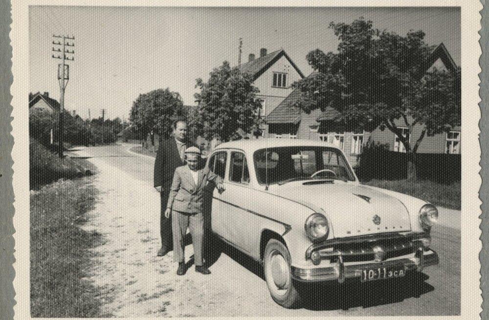 Mees ja poiss Olustvere tänaval sõiduauto Moskvitš kõrval.