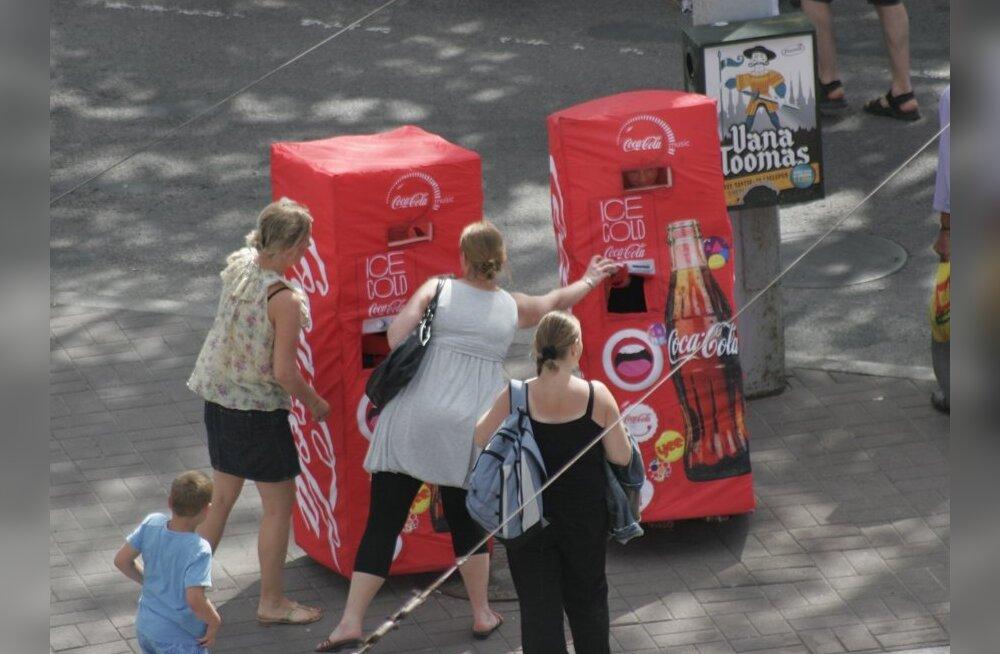 Inimesed Coca-Cola-kujulistes kostüümides inimestelt karastusjooki pinnimas.