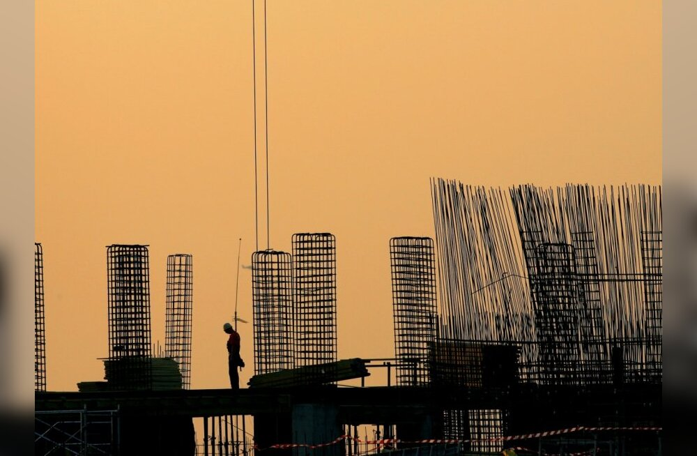 File - In this Aug. 6, 2008 file photo a worker pauses at dusk on top of a building under construction in Bucharest, Romania.   Romania's sorry real estate saga is a reflection of the headwinds from the global economic turmoil still facing Eastern Europe,