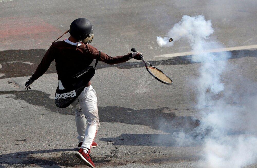 Politseinikud tulistavad demonstrante pisargaasiga, nemad aga korjavad tossava pisargaasigranaadi üles ja löövad tennisereketiga politseinikele tagasi.