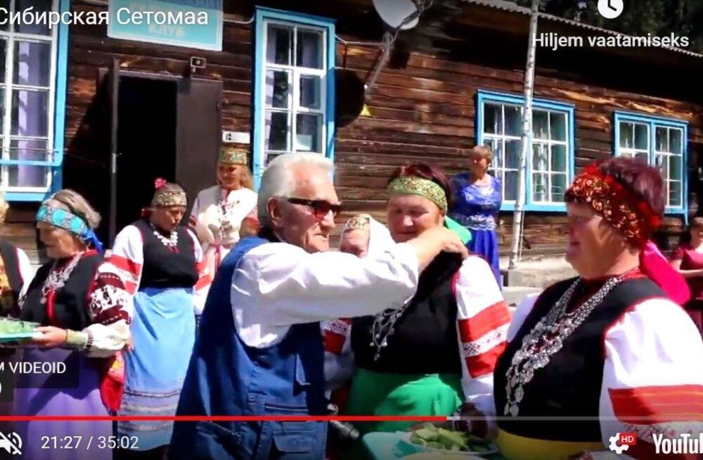"""Maalehe reisijuht Kuno Raude Siberis, tervitajateks Haida külanaised, kaader filmist """"Siberi Setomaa"""""""