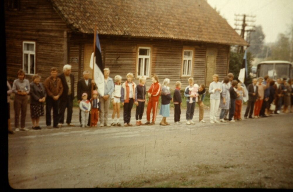 Paarikümnest inimesest koosnev suguvõsa seisab Lilli külas oma maja vastas keset maanteed. Lippu hoiab Heikki Lenk koos lastelastega. Tema kõrval seisavad pojad ja abikaasa. Reas on eri vanuses lapsi, kõik praeguseks 30 aastat vanemad. Noorim oli toona viiekuune.