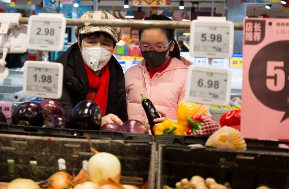 Kaitsemaskidega ostjad Pekingi supermarketis.