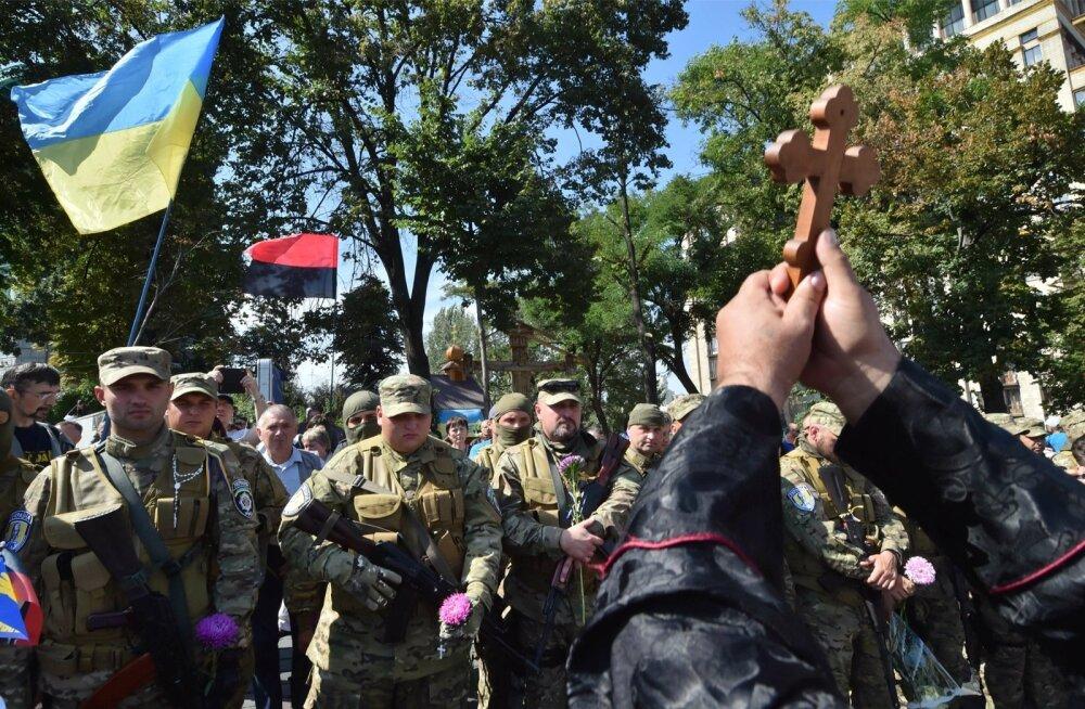 Relvajõud ja jumala arm. Preester õnnistab 2014. aasta sõjasuvel Ukraina vabatahtlikke.