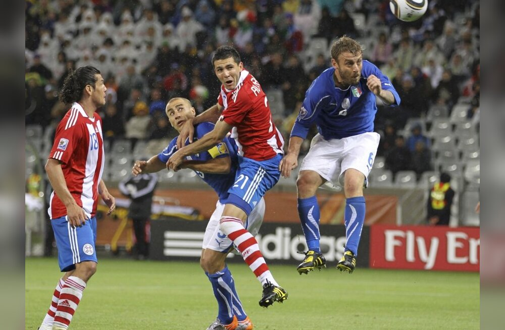 Paraguay's Antolin Alcaraz heads in a goal during their 2010 World Cup Group F soccer match against Italy at Green Point stadium in Cape Town June 14, 2010, as Fabio Cannavaro  (2nd R) and Daniele De Rossi  (R) looks on.     REUTERS/Carlos Barria (SOUTH A