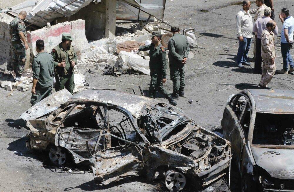 Süüria relvajõudude esindajad õhkulastud auto kõrval.