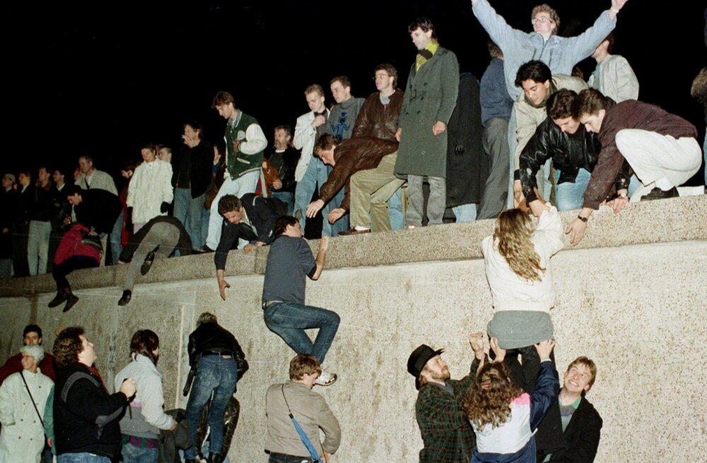 Ida- ja Lääne-Saksamaa kodanikud ronivad Berliini müürile tähistama Brandenburgi väravate avamist 9. novembril 1989. aastal.
