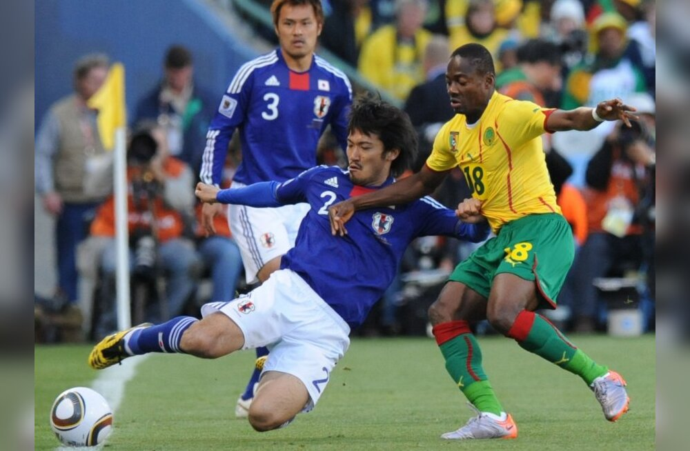 Cameroon's midfielder Eyong Enoh  (R) fights for the ball with Japan's midfielder Yuki Abe (C) as Japan's defender Yuichi Komano (back) looks on  during their Group E first round 2010 World Cup football match on June 14, 2010 at Free State stadium in Mang