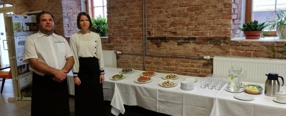 Abikoka kursuse kaks õpilast tutvustamas Läti külalistele pakutavat toitu.