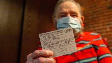 81-aastane USA veteran hoiab käes vaktsineerimiskaarti