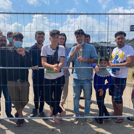 Druskininkai laagri immigrandid nurisevad elutingimuste üle, kuid poseerivad hea meelega kaamerale. Jutt ebainimlike olude kohta aga jätkub.
