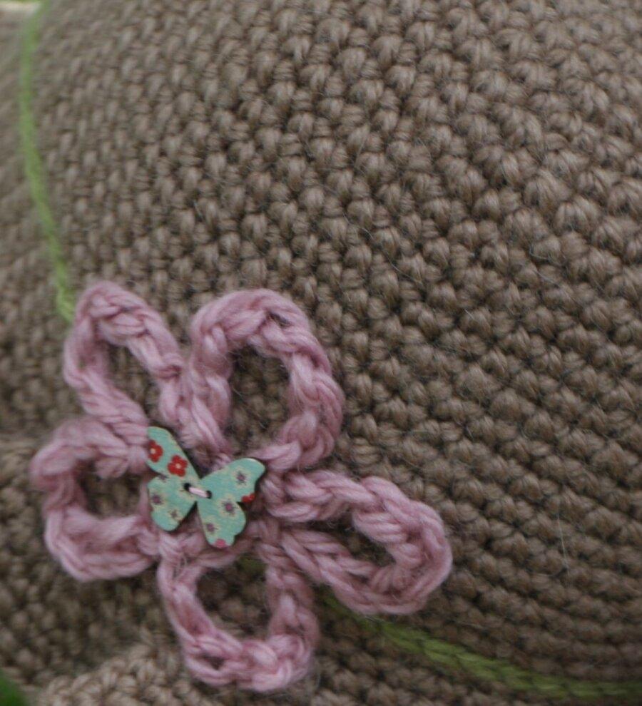 10928a8debf Pruunis toonis mütsile annavad viimase lihvi pastelsetes toonides  heegeldatud pael ning lilleke.