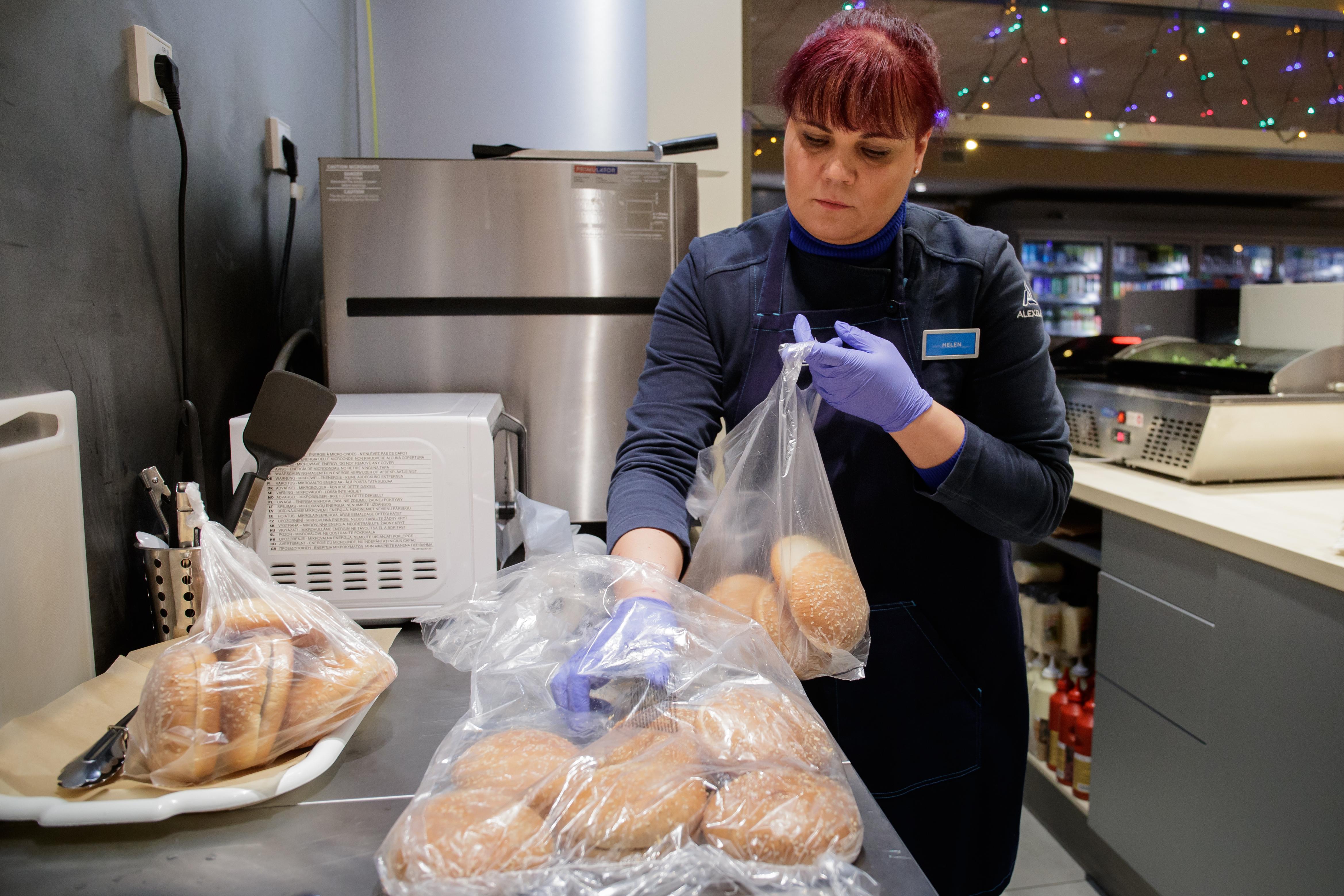 Helen täidab sahtleid burgerisaiadega. Taustal on näha jõulutuled, mis tanklasse pühademeeleolu loomiseks on pandud.